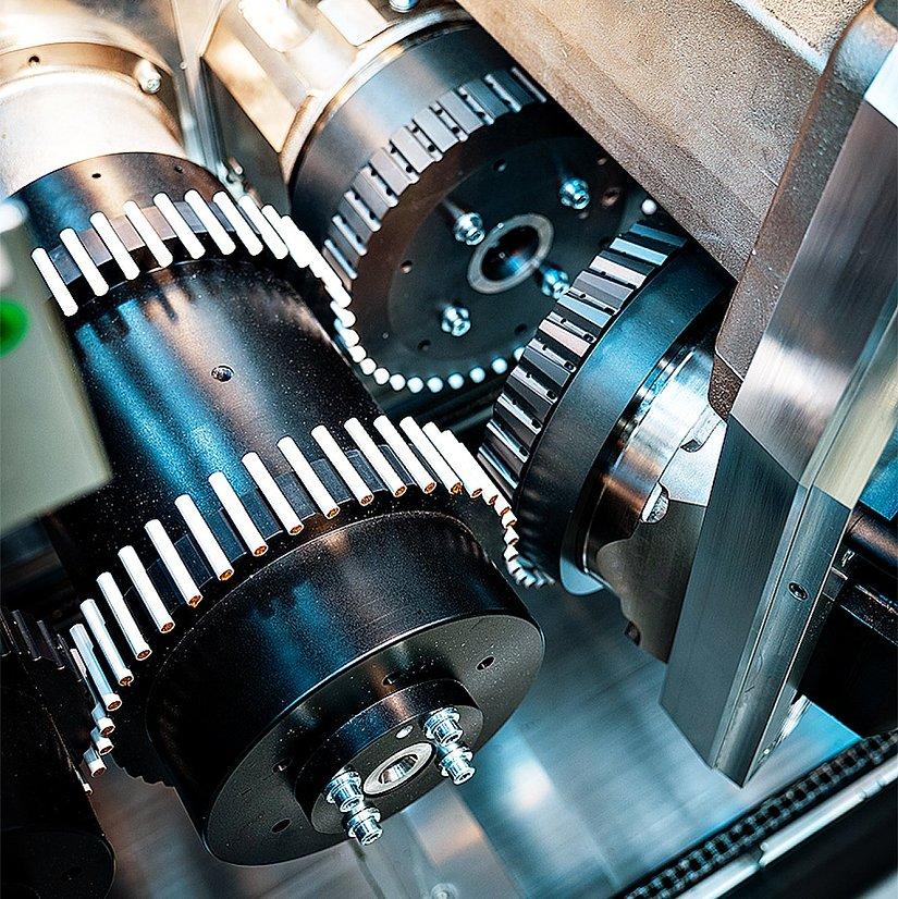 In einer geöffneten Maschine, dem Multi Segment Maker, sind Zahnrad-Walzen zu sehen.