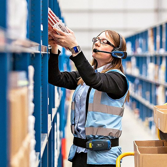 Photo of men and women putting together orders in a warehouse, they are wearing headsets