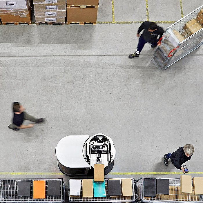 Aerial view of two Toru robots moving between workers in a high-bay warehouse.