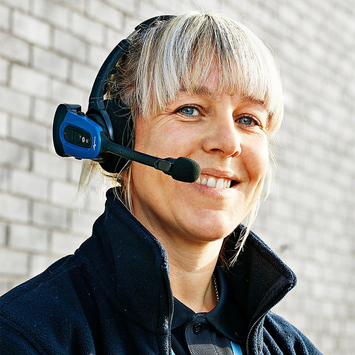 A smiling woman wearing a headset