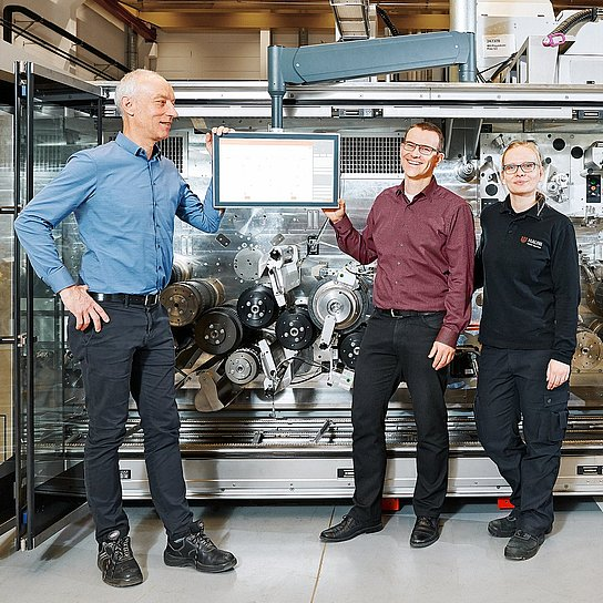 Photo of Hauni employees Karsten Barsch, Christian Junge and Nina Gröncke in front of a machine, the multi-segment maker