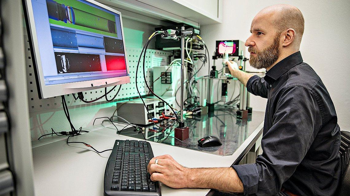 Foto eines Ingenieurs im Laboram Computer nehen einem Aufbau von Messinstrumemten