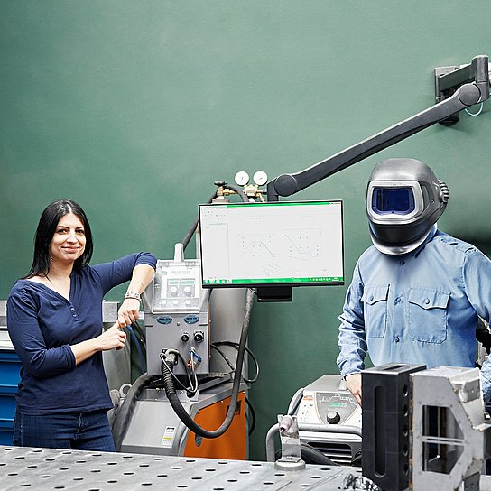 Employees Béata Szolnok and Ferenc Brozovac are standing at a welding workstation at Hauni Hungary