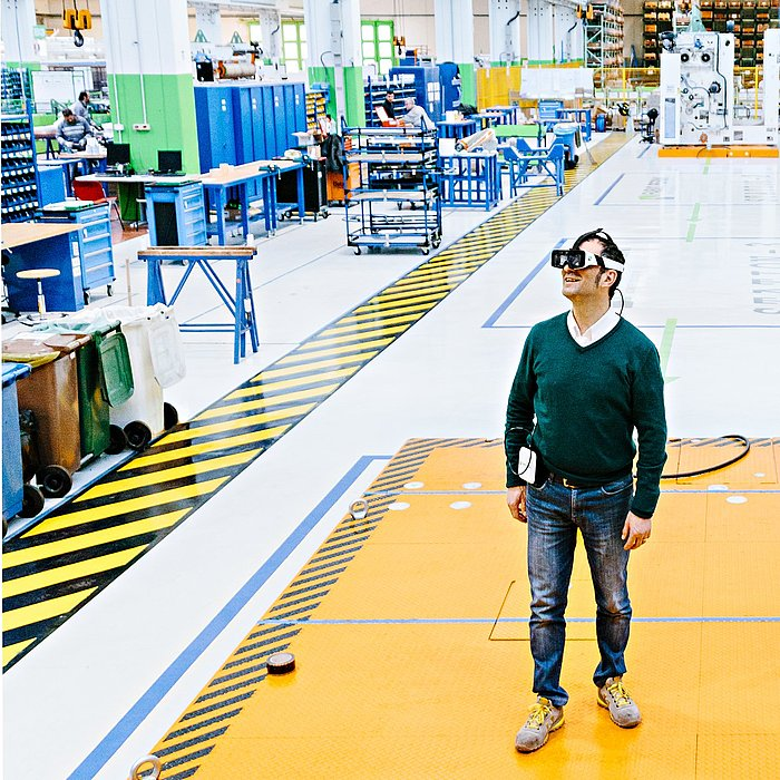 Foto von Giulio Ricci, der mit Weareable Glasses in der Produktionshalle von Fabio Perini in Lucca steht