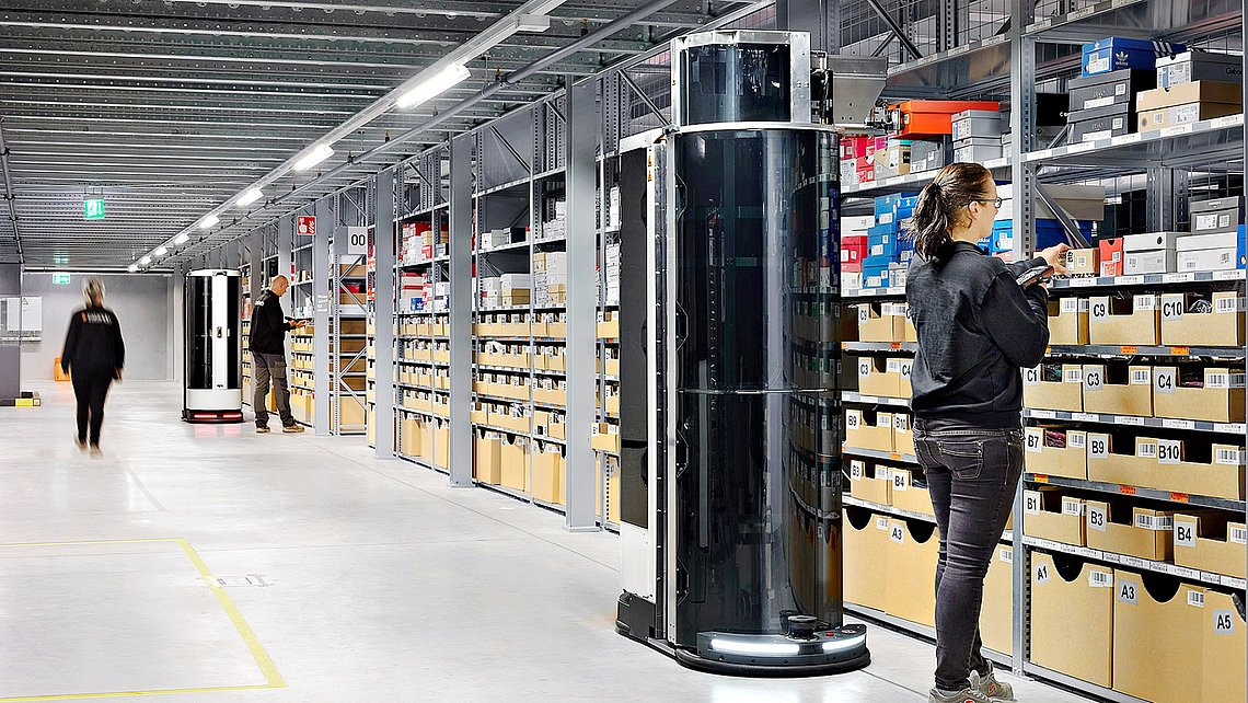 Photo of the Toru robot working next to humans in a high-bay warehouse.