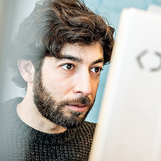 Portrait photo of Gerardo Lopez, Interface Designer at Körber Digital, working at the computer