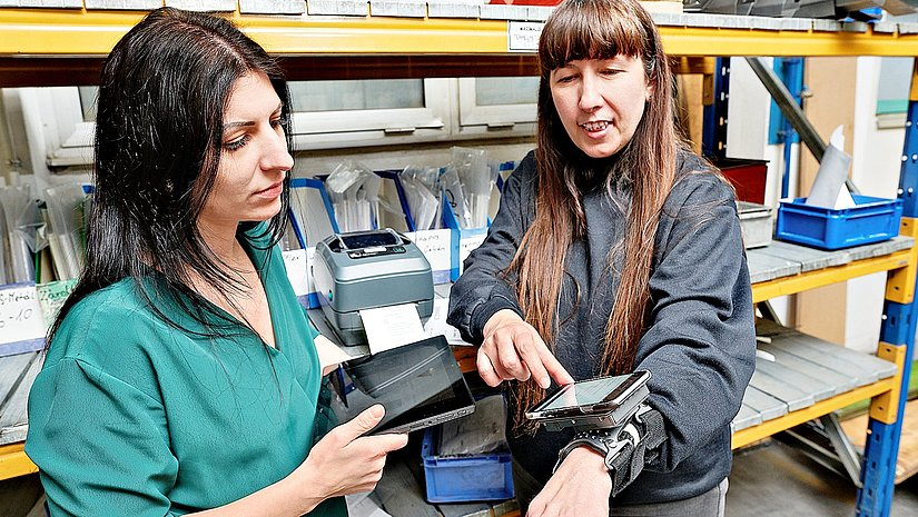 Photo of Beáta Szolnok and Regina Kövesdi, standing in a warehouse, working with tablet and hand scanner.