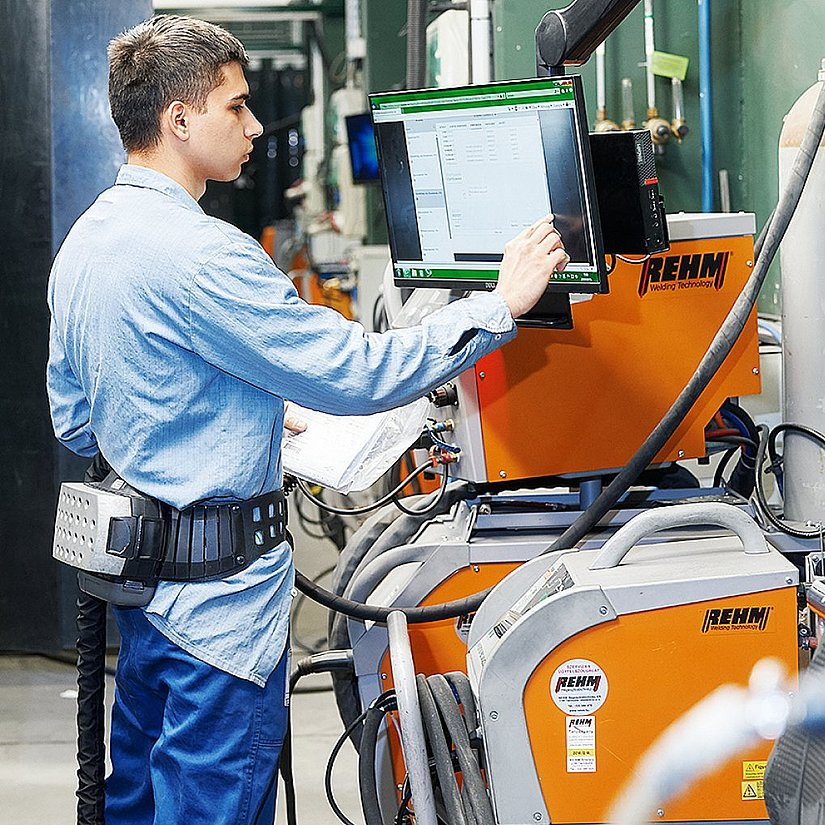 Photo of the welder Ferenc Brozovácz working on a touch screen.